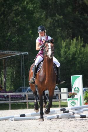 latvia girls: RIGA, LATVIA - AUGUST 12: Latvian rider Tija Alīse Jurjāne show jumps at the Latvian Horse Days 5 and knocking down the barrier on august 12, 2012, Inchukalns, Latvia