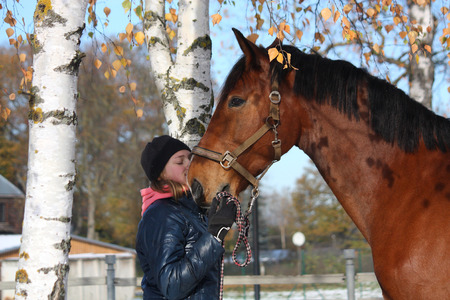 herbivore: Beautiful teenager girl and bay horse portrait in autumn with snow on the ground
