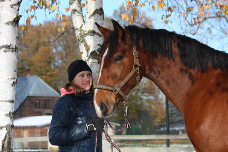 Beautiful teenager girl and bay horse portrait in autumn with snow on the ground photo
