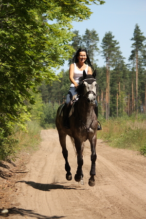 gray horse: Beautiful woman riding gray horse near the forest Stock Photo