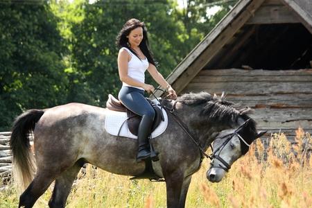 Portrait der schönen jungen Frau auf dem Pferd in der Nähe der Scheune