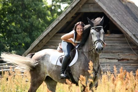 Portrait of beautiful young woman on horse near the barn Stock Photo