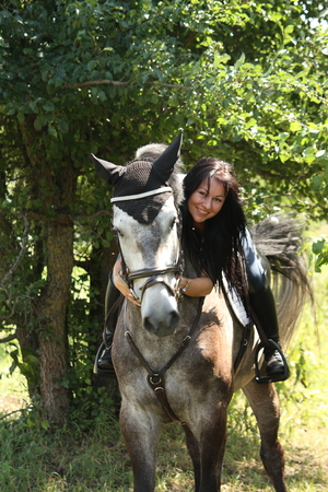 gray horse: Portrait of beautiful young woman and gray horse in garden
