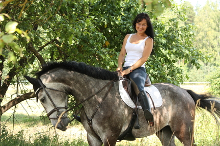 black cowgirl: Portrait of beautiful young woman and gray horse in garden