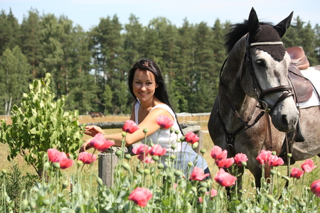 black cowgirl: Beautiful woman in the blooming garden with gray horse Stock Photo