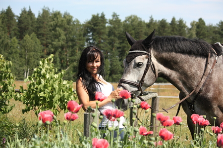 gray horse: Beautiful woman in the blooming garden with gray horse Stock Photo