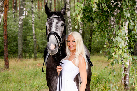 horse blonde: Beautiful blonde woman and gray horse in forest portrait