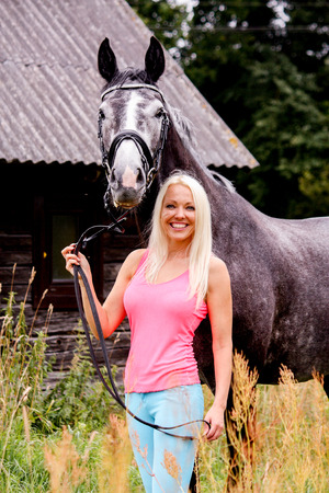 horse blonde: Beautiful blonde woman and her horse in rural area in summer Stock Photo