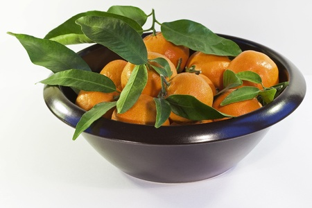 stoneware: A brown stoneware bowl with tangerines and leaf on a white background