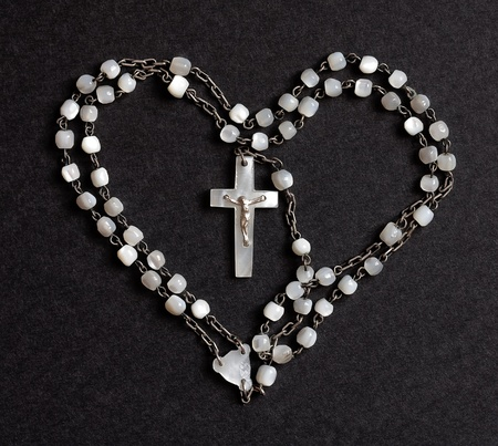 sacred heart: One old rosary shaped as a heart with the crucifix in the middle Stock Photo