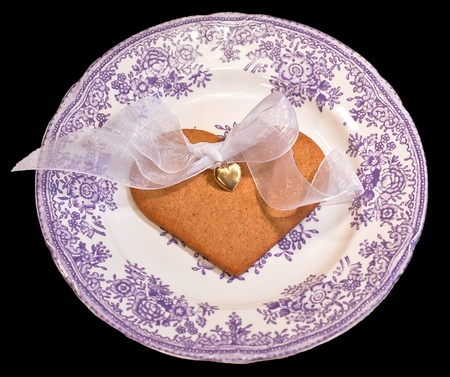 Goldheart with ribbon  on a gingerbread on an old plate isolated on black photo
