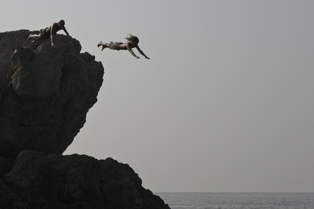 alupka: Alupka, Ukraine - August, 18, 2010. Two unidentified young men jumped into the sea from a cliff. The action took place in Alupka on the beach