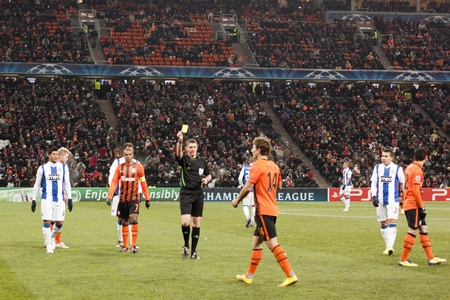 DONETSK, UKRAINE - NOVEMBER 23, 2011: Referee Craig Thomson (SCO) shows a yellow card Vasyl Kobin (No. 14, Shakhtar) in the match of the Champions League FC Shakhtar Donetsk vs. FC Porto in Donetsk Donbass Arena on November 23, 2011.