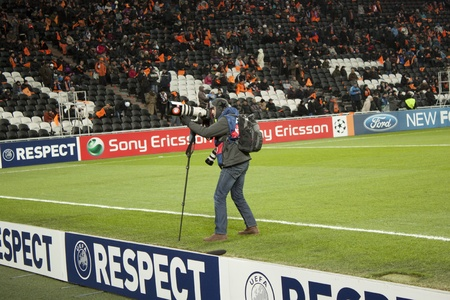 donbass: DONETSK, UKRAINE - NOVEMBER 23, 2011: Unidentified photographer taking pictures Donbass Arena tribunes before the match of the Champions League FC Shakhtar Donetsk vs. FC Porto in Donetsk on November 23, 2011. Editorial