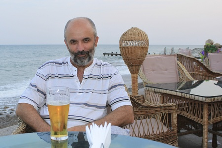 Middle-aged man at a table in a cafe by the sea photo