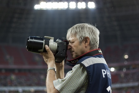 DONETSK, UKRAINE - JULY 10, 2011. Unidentified professional sports photographer during the first match of Championship of Ukraine 2011-2012 in Donbass Arena between Shakhtar Donetsk and Kiev Obolon.