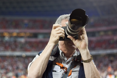 DONETSK, UKRAINE - JULY 10, 2011. Unidentified professional sports photographer during the first match of Championship of Ukraine 2011-2012 in Donbass Arena between Shakhtar Donetsk and Kiev Obolon. 報道画像
