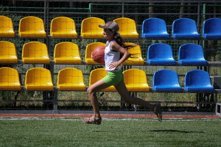 SVIATOHIRSK, UKRAINE - JULY 30, 2012: Unidentified girl runs with ball during the relay race in the children
