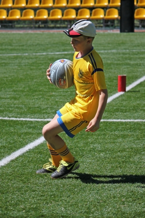 SVIATOHIRSK, UKRAINE - JULY 30, 2012: Unidentified boy runs with ball during the relay race in the children