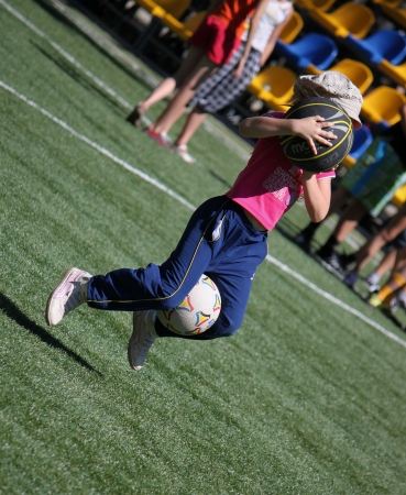 SVIATOHIRSK, UKRAINE - JULY 30, 2012: Unidentified child with two balls in a fun relay race in the children