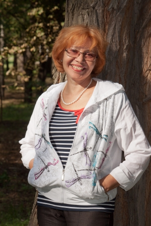 Middle-aged woman in glasses smiling near big tree Stock Photo