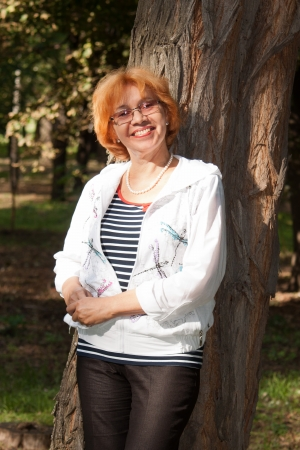 Middle-aged woman smiling near big tree