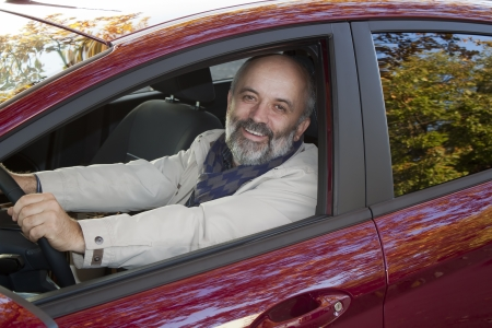 Middle-aged man with a beard driving a hot magenta car photo