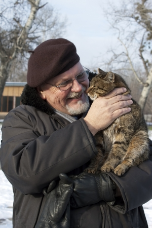 Middle-aged man with a beard smiling, holding a cat Stock Photo