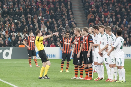 DONETSK, UKRAINE - NOVEMBER 5, 2013 Referee William Collum SCO pushes a wall of players Leverkusen in the Champions League match in Donetsk Donbass Arena November 5, 2013 The match between FC Shakhtar Donetsk and Leverkusen ended in a goalless draw Editorial