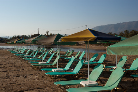Free turquoise loungers under umbrellas on the sandy beach of Georgioupolis, Crete, Greece photo