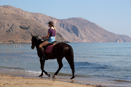 vacationers: GEORGIOUPOLIS, CRETE, GREECE - JULY 31, 2013  Unidentified rider on a horse on the beach  Horseback riding in Crete one of the favorite pastimes of vacationers