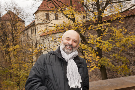 A middle-aged man smiling on a background of autumn trees in the Prague Castle
