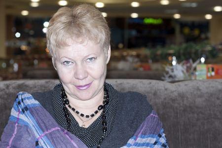 Portrait of mature woman sitting on a couch in a restaurant
