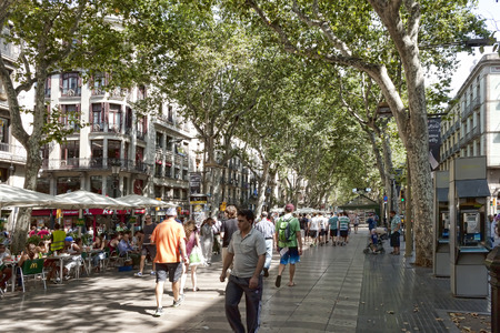 BARCELONA, SPAIN - JULY 13, 2013: Rambla - a pedestrian street in the center of Barcelona. There is always a lot of tourists