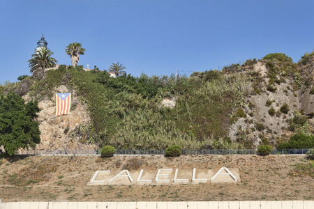 pharos: The name of the city on a hill near the beach. Calella on July 18 2013  a popular holiday destination of tourists from all European countries Stock Photo