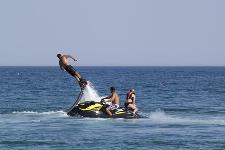 turkish man: CAMYUVA, KEMER, TURKEY - JULY 16, 2015: Unidentified Turkish man demonstrates flyboard acrobatics on the beach of Camyuva. Extreme water sports are increasingly popular on the beaches of Turkey