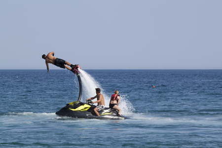 turkish man: CAMYUVA, KEMER, TURKEY - JULY 16, 2015: Unidentified Turkish man demonstrates flyboard acrobatics on the beach of Camyuva. Extreme water sports are increasingly popular on the beaches of Turkey