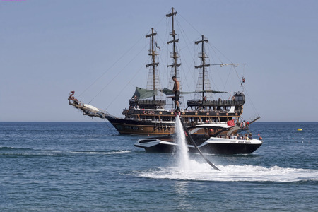 schooner: CAMYUVA, KEMER, TURKEY - JULY 16, 2015: On the coast of Turkey widespread various marine activities. Among them flyboard, walks on boats and yachts, stylized pirate schooner Editorial