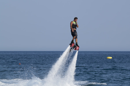 CAMYUVA, KEMER, TURKEY - JULY 12, 2015: Unidentified Turkish man hovered above the water. Extreme water sports are increasingly popular on the beaches of Turkey