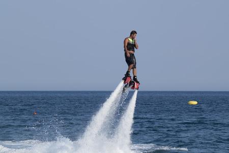 increasingly: CAMYUVA, Kemer, Turchia - 12 luglio 2015: non identificato uomo turco aleggiava sopra l'acqua. Sport acquatici estremi sono sempre pi� popolari sulle spiagge della Turchia