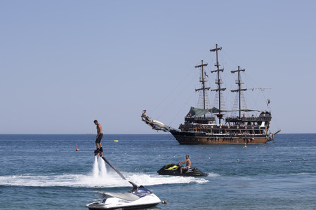 schooner: CAMYUVA, KEMER, TURKEY - JULY 16, 2015: On the coast of Turkey along with the traditional personal watercraft are becoming popular flyboard and yachting stylized pirate schooner Editorial