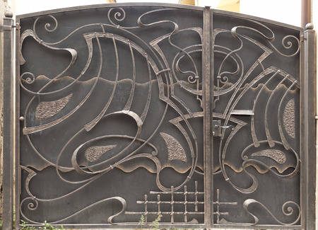 Closed large metal gates with wrought iron ornaments