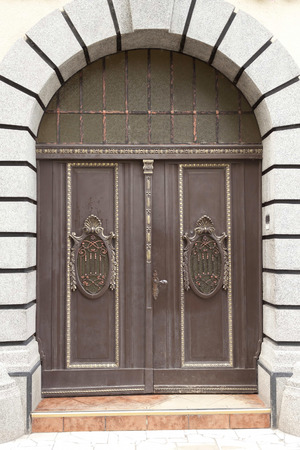 large doors: Large closed doors with carved wood and metal inlays Stock Photo