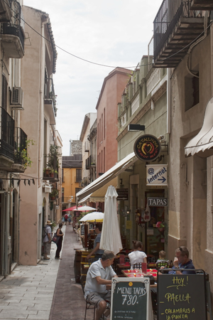 salvador dali: FIGUERAS, SPAIN - JULY 17, 2013: Narrow streets of Figueres, near the Museum of Salvador Dali. Many cafes are always full of tourists Editorial
