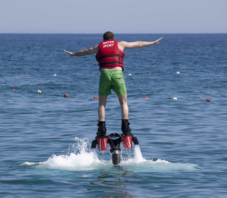 increasingly: CAMYUVA, KEMER, TURKEY - JULY 16, 2015: Unidentified Turkish man studying extreme flyboard. Extreme water sports are increasingly popular on the beaches of Turkey Editorial
