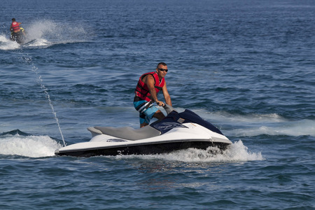 increasingly: CAMYUVA, KEMER, TURKEY - JULY 16, 2015: Unidentified Turkish man glides over the waves of the Mediterranean Sea on Jet Ski. Extreme water sports are increasingly popular on the beaches of Turkey