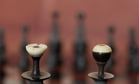 Carved wooden chess pieces with bone tips Stock Photo