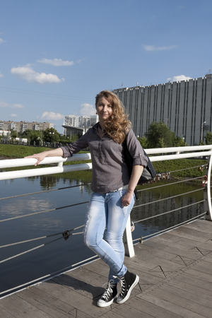 full height: Young stylish woman in jeans and sneakers, on the bridge at full height