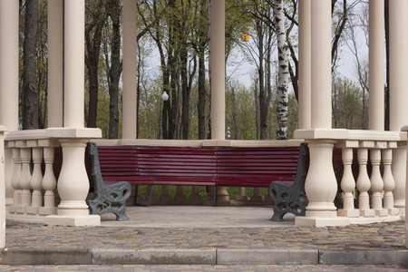 gazebo: Column gazebo with empty benches in the park. Spring morning