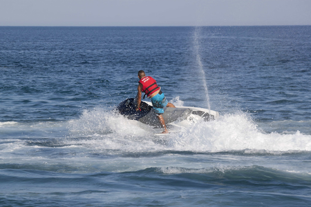 personal watercraft: CAMYUVA, KEMER, TURKEY - JULY 16, 2015: Unidentified Turkish man glides over the waves of the Mediterranean Sea on Jet Ski. Extreme water sports are increasingly popular on the beaches of Turkey